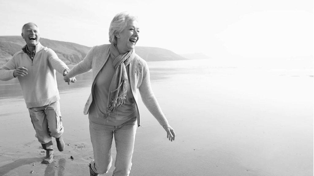 Happy retired couple on the beach.